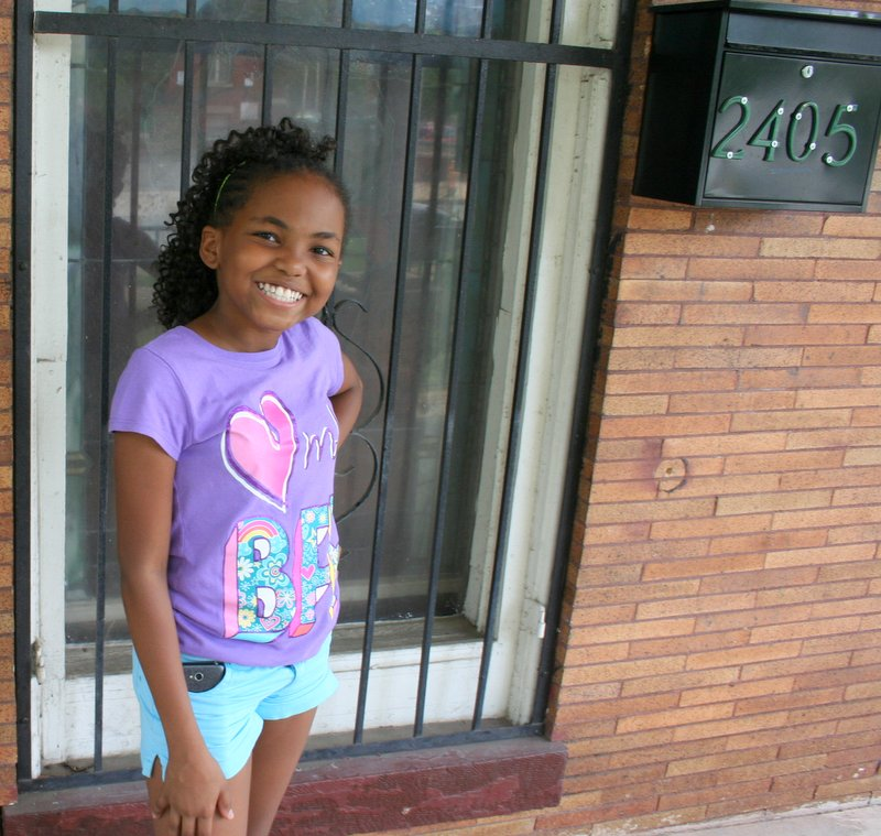 11-year-old Asia, on the porch of the St. Francis Center, talks about her ideas for the Community Resource Fair.  (Photo by Danielle Sweeney)