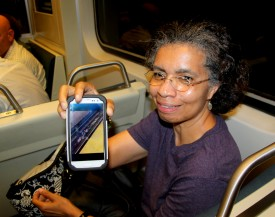 Metro rider Carol Cooke shows photos of trash on the tracks. (Photo by Fern Shen)