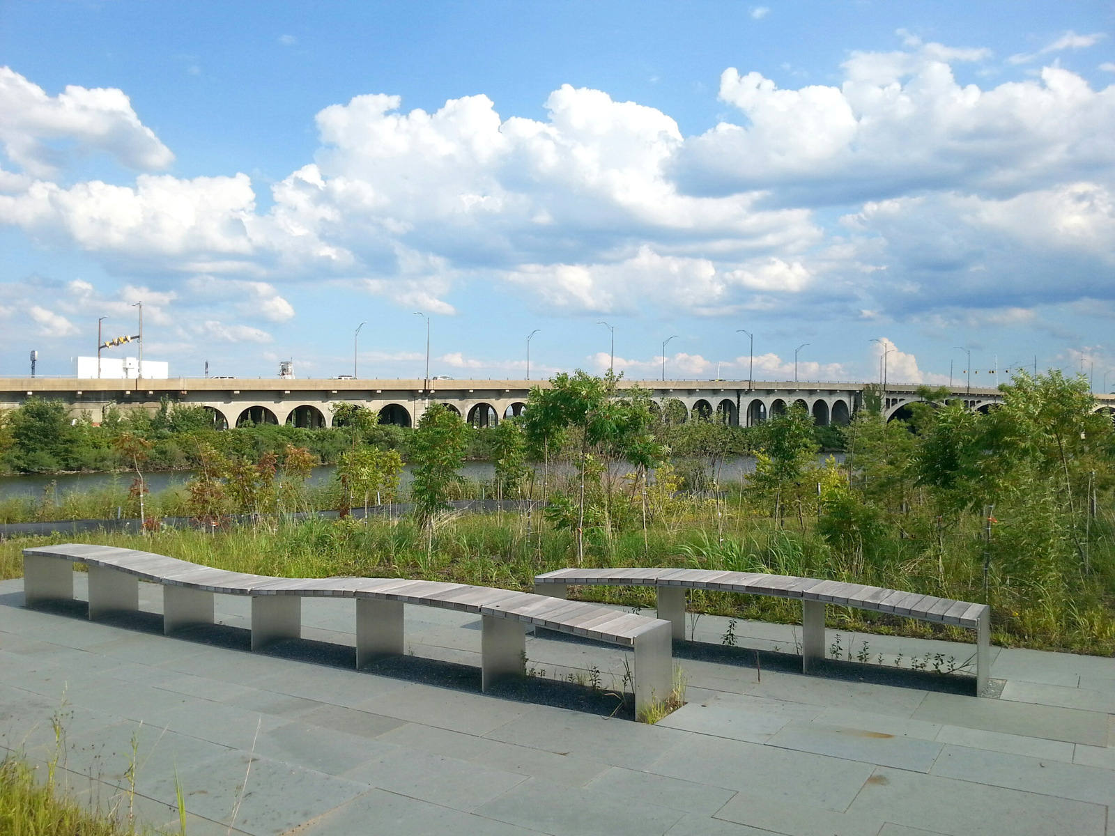 Weeds grow under benches at the fenced-off park constructed with public funds. In background is the Hanover Street Bridge. (Photo by Ed Gunts)