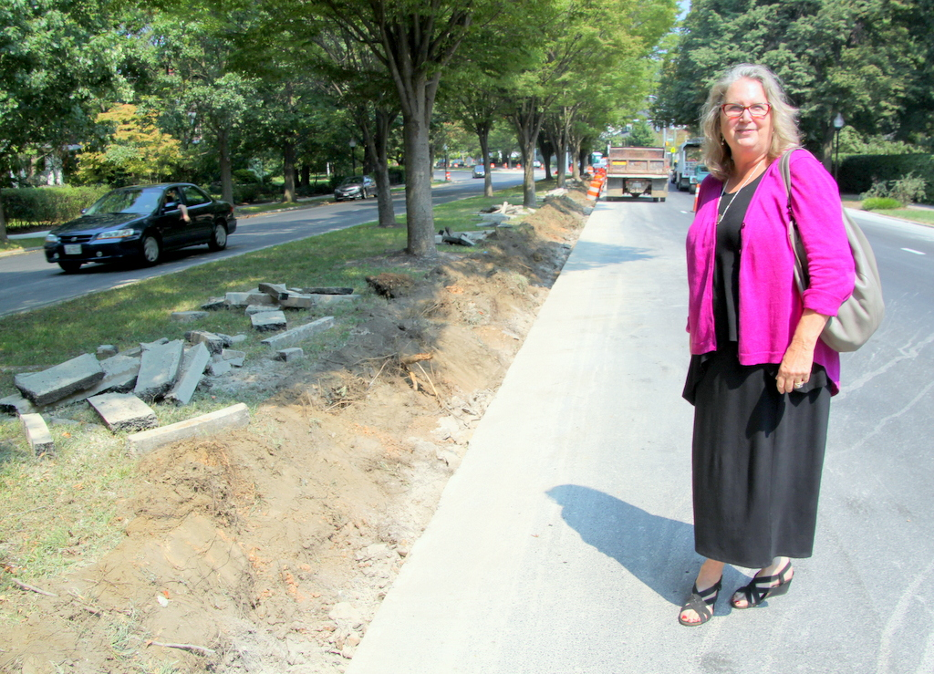 Barbara Marx Brocato stands on Roland Avenue near where her front yard has been flooded with runoff from the street. (Photo by Fern Shen)