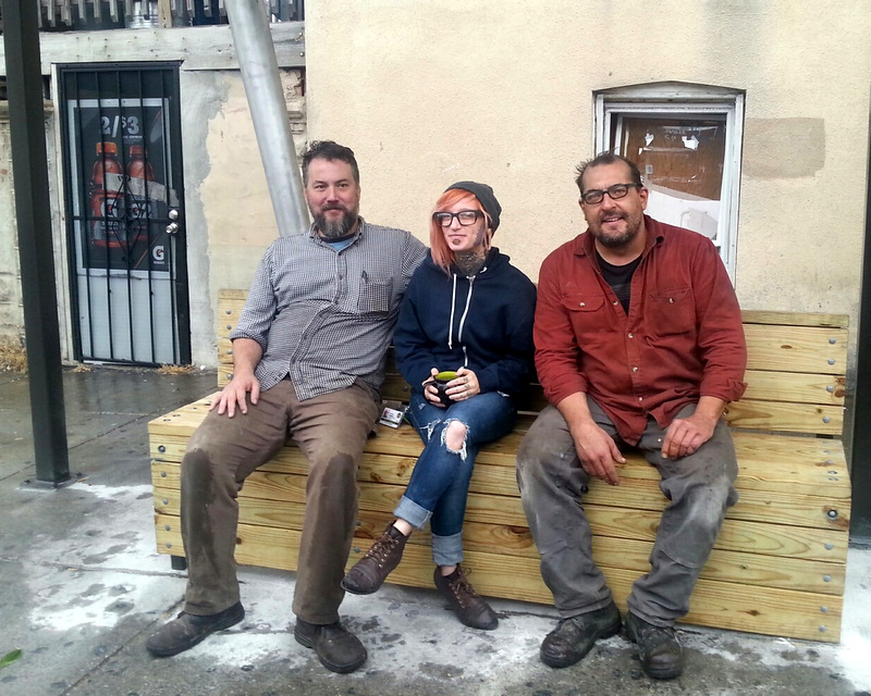 The artists relax after finishing Baltimore's latest bus stop sculpture: from left, Kyle Miller, Rachel Timmins and Tim Scofield. (Photo by Ed Gunts)