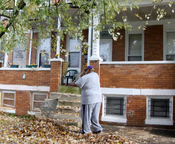 Francois Abdool outside the Park Heights Avenue house his family owns (at far right) thatis slated for demolition. (Photo by Fern Shen)