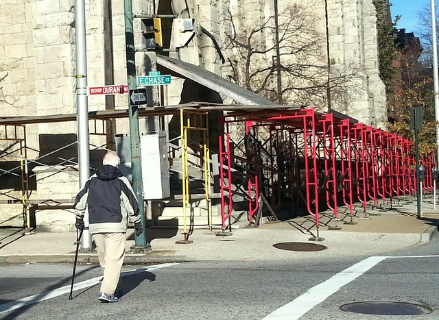 A man approaches the the scaffolding on St. Paul Street. The Chase Street block is named after the church's pastor and CEO. (Photo by Ed Gunts)