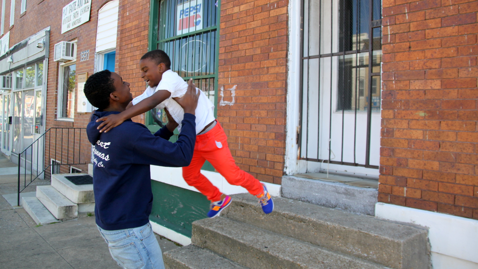 Along the march route, Malik Creighton, 6, leaps into the arms of his brother Brian Rice, 14. (Louie Krauss)