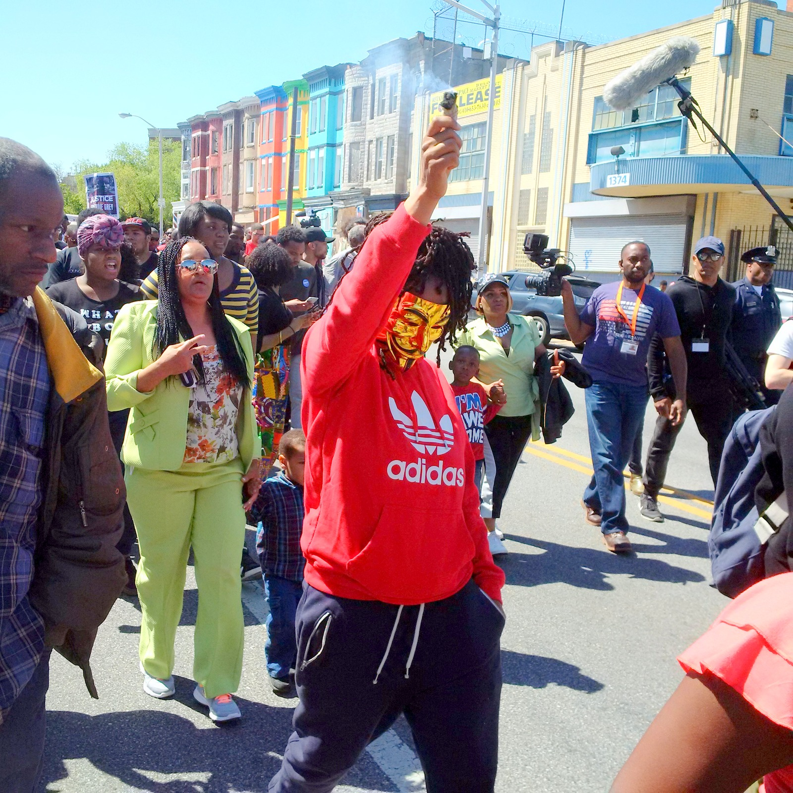 Joint uplifted, a woman walks down North Avenue as part of the