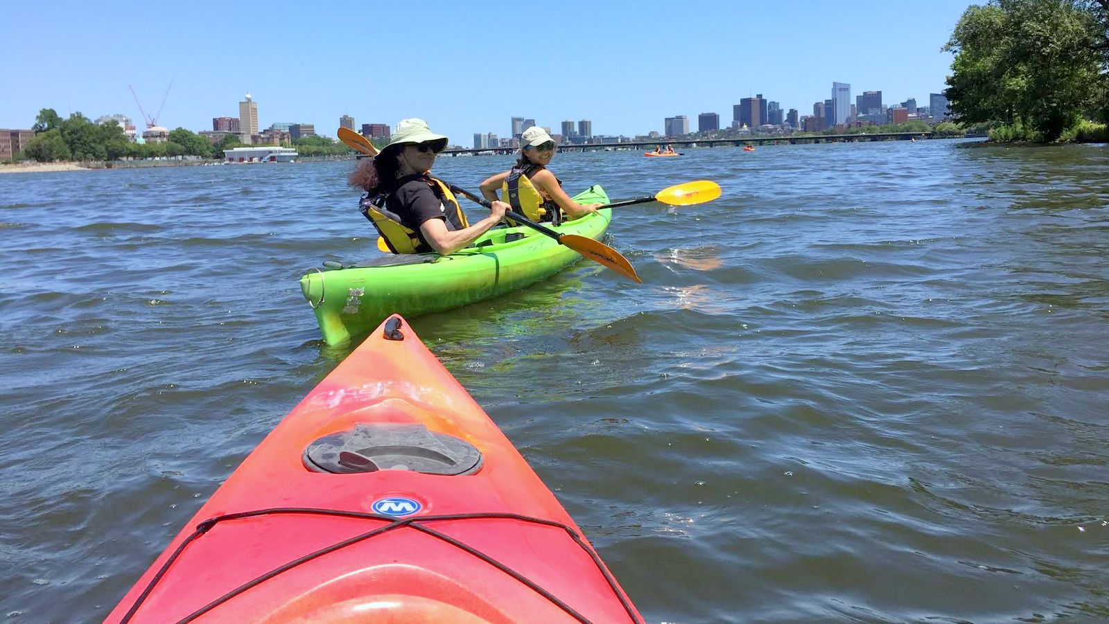 The author, with niece Carly Dennis, paddle a sparkling and clean-seeming Charles River last month. In the distance, the Boston skyline. (Andy Shen)
