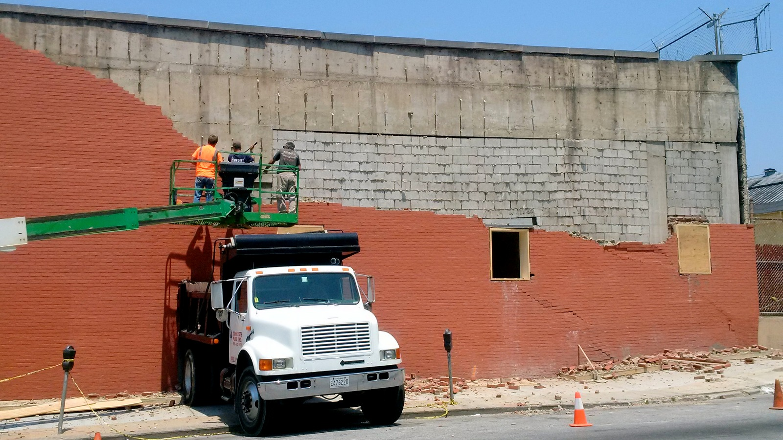 On May 29, workers remove the brick facade of the Preston Street building. (Fern Shen)