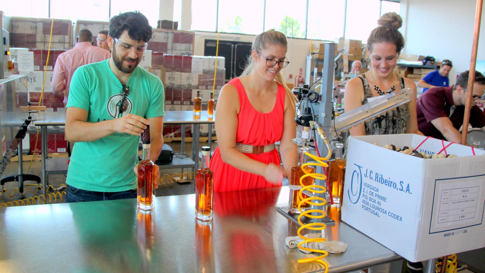 Volunteers demonstrated the labeling process for Sagamore Spirit rye. The whiskey distillery is one of many businesses that are part of the Port Covington project. (Fern Shen)