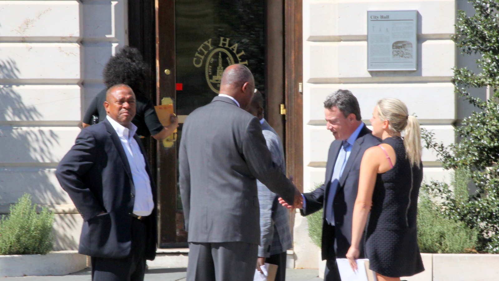 Seconds after telling reporters he supports the Port Covington TIF, Carl Stokes clasps hands with the developer's attorney, Jon Laria. (Fern Shen)