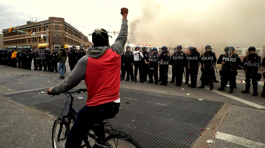 A demonstrator raises his fist against a phalanx of police stationed at Penn-North in April 2015. (youthkiawaaz.com)