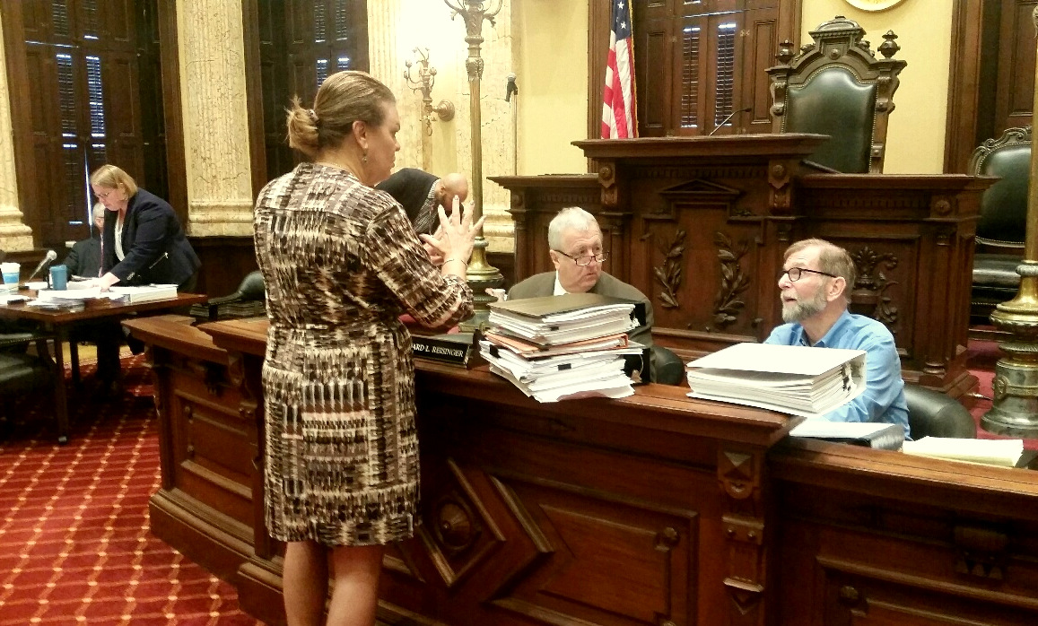 Councilmembers Sharon Green Middleton, Ed Reisinger and Jim Kraft talk during a recess. The record of the committee's zoning amendments are in the loose-leaf notebooks. (Mark Reutter)