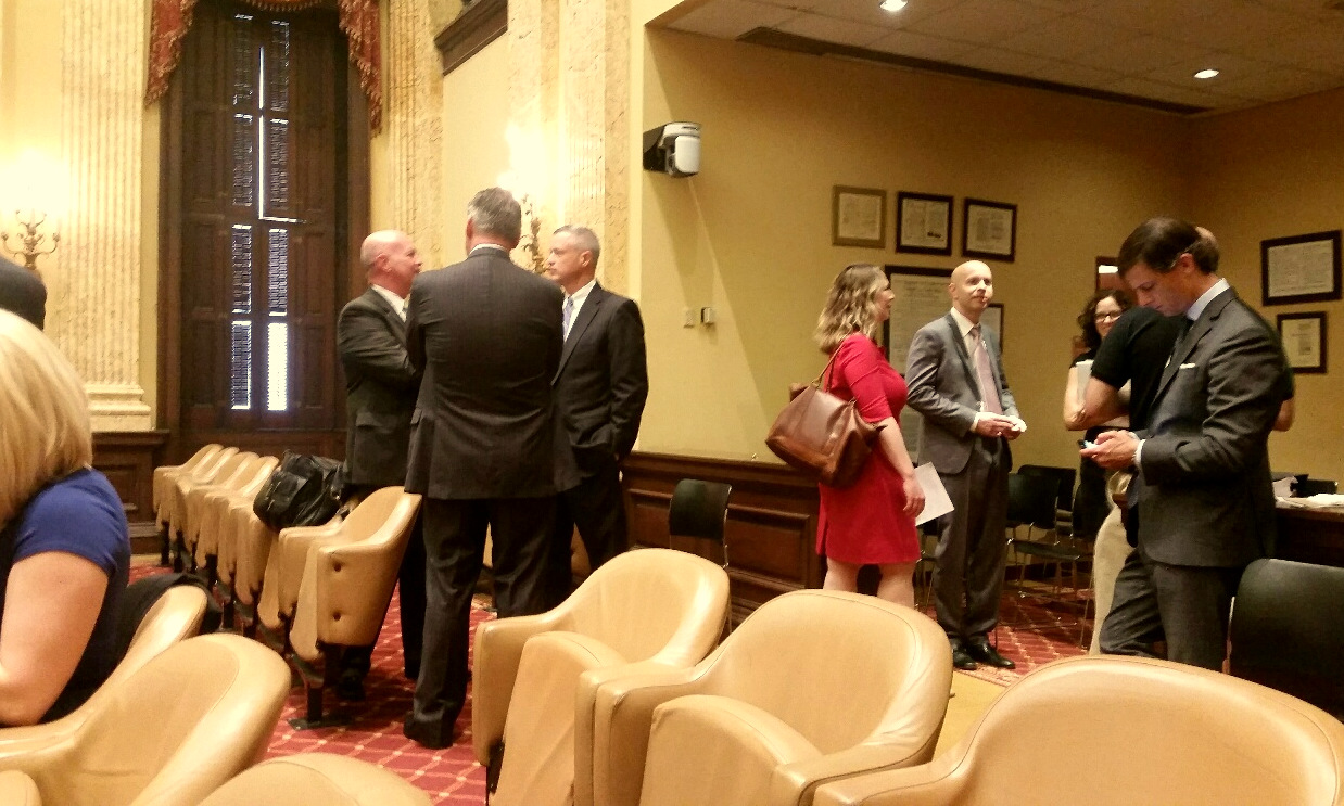 Before a markup session of the bill, lawyers and lobbyists congregate in the Council chambers. Among them: Sean Malone (back to camera), Peter O'Malley, Caroline Hecker, Ryan Potter and Adam Baker. (Mark Reutter)