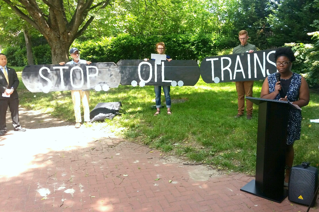 A rally staged last June above the tunnel where the CSX train derailed last June. The speaker is Destiny Watford, a recipient of the Goldman Environment Prize; to the far left Del. Clarence K. Lam, a doctor who has pushed statewide for better oil train regulation. (Mark Reutter)