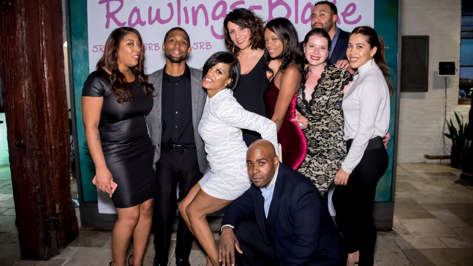 Rawlings-Blake, in white, poses with guests including Brandon Scott (2nd from left) and Kaliope Parthemos (back row, center)