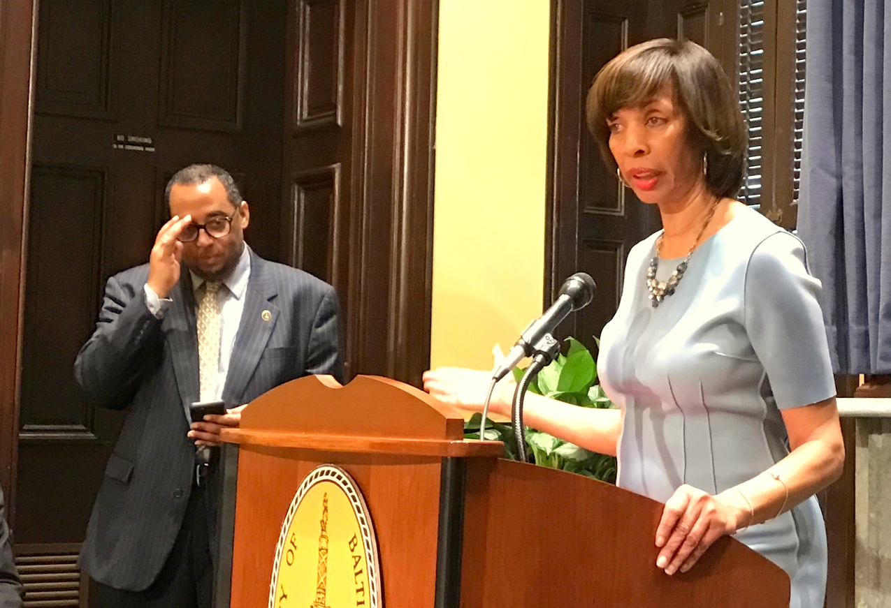 Mayor Catherine Pugh speaks to reporters today, with her spokesman, Anthony McCarthy, standing nearby. (Mark Reutter)