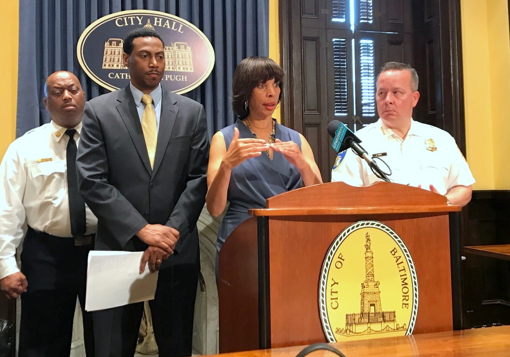 Acting Solicitor David Ralph listens to Mayor Catherine Pugh speak today about police overtime. To the mayor's left is Police Commissioner Kevin Davis and in the background is Fire Chief Niles R. Ford. (Mark Reutter)