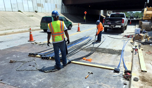 With the errant pipe repaired, workers reinstall the surface of Desoto Road. (Baltimore DPW)
