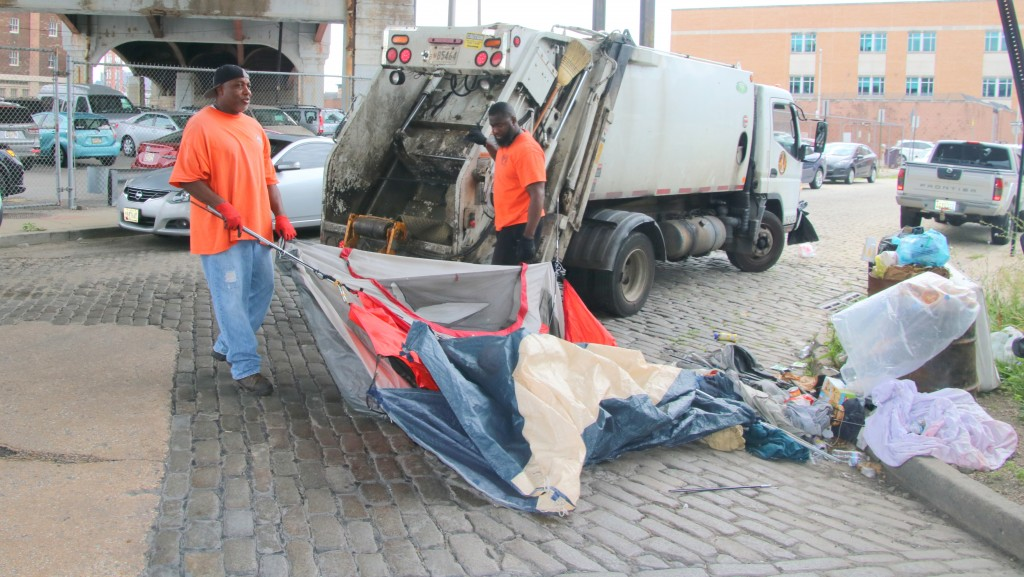 City workers said this tent being hauled off had been on the refuse pile residents had raked up and had not been occupied. (Fern Shen)