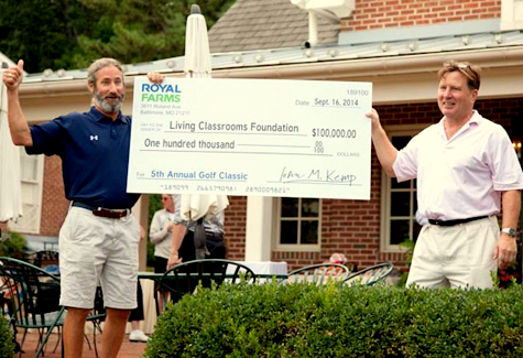 Living Classrooms CEO James Piper Bond accepts $100,000 from Royal Farm's President John Kemp. The money was raised at a charity golf tournament. (Royal Farms Foundation)