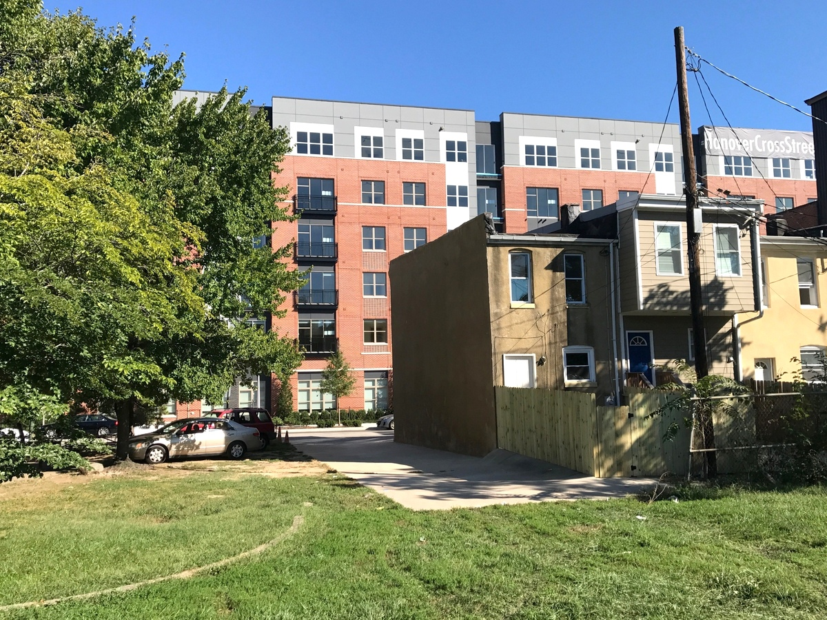 From Solo Gibbs Park, a view of several historic rowhouses of the original community and Stadium Square's newly opened Hanover Cross Street apartment building. (Mark Reutter)