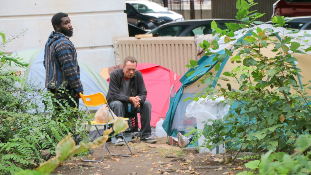 At the encampment on Guilford Avenue, Carl Banks (l) visits with another resident. (Fern Shen)