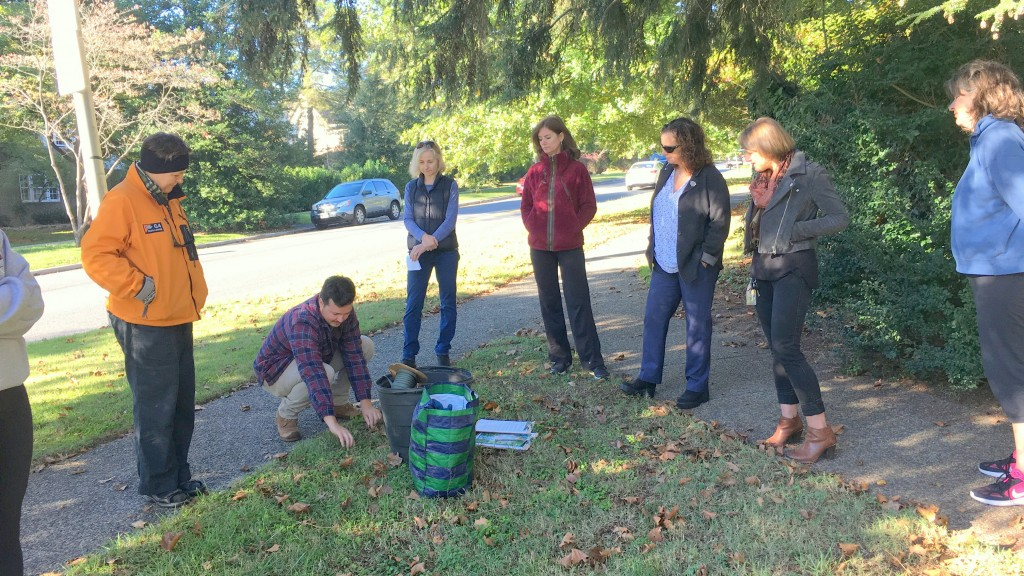 Eric Sargent, of the Baltimore Orchard Project, explains the process to neighbors planting two cherry trees in memory of Molly Macauley. (Fern Shen)