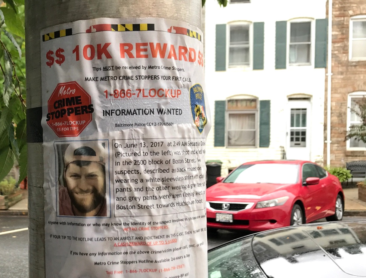 A crumpling poster advertising a reward for information leading to the apprehension of Sebastian Dvorak's killers. Was this shooting connected to the street robberies in Upper Fells Point? (Mark Reutter)