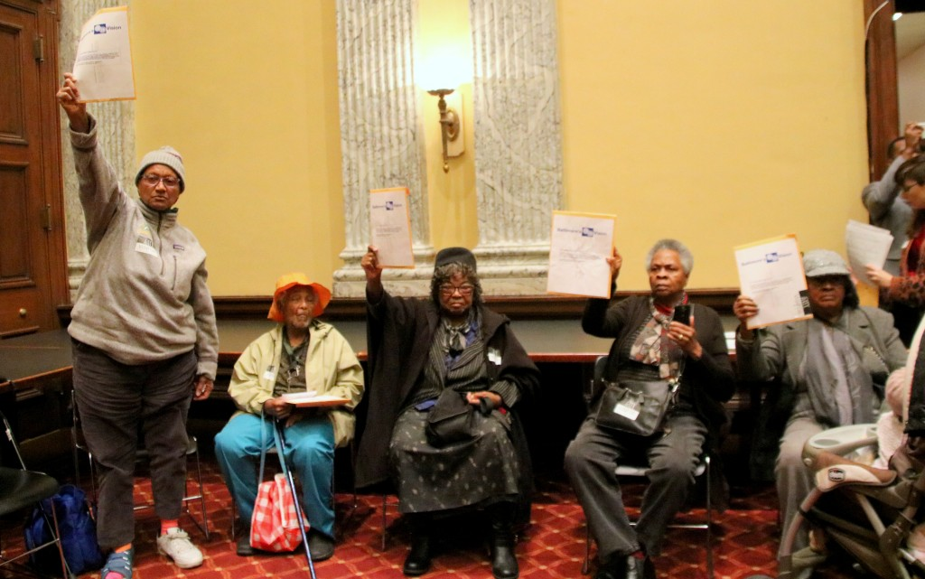 Showing support for more funding for affordable housing, women raise the 20/20 agenda high. (Fern Shen)