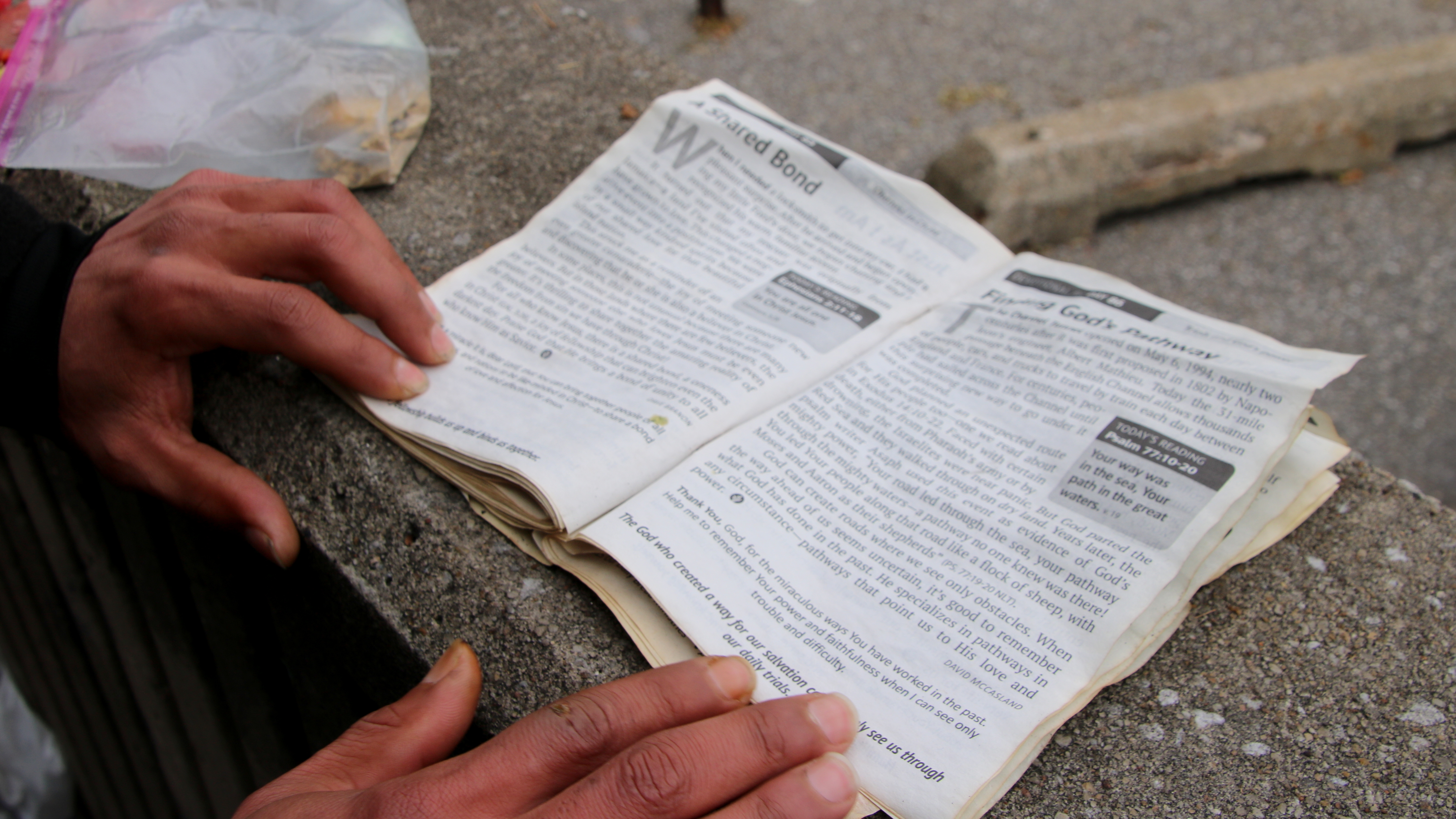 Namid Rawls uses a concrete ledge beside the city parking lot to hold his toothbrush, candles and religious reading material. (Fern Shen)