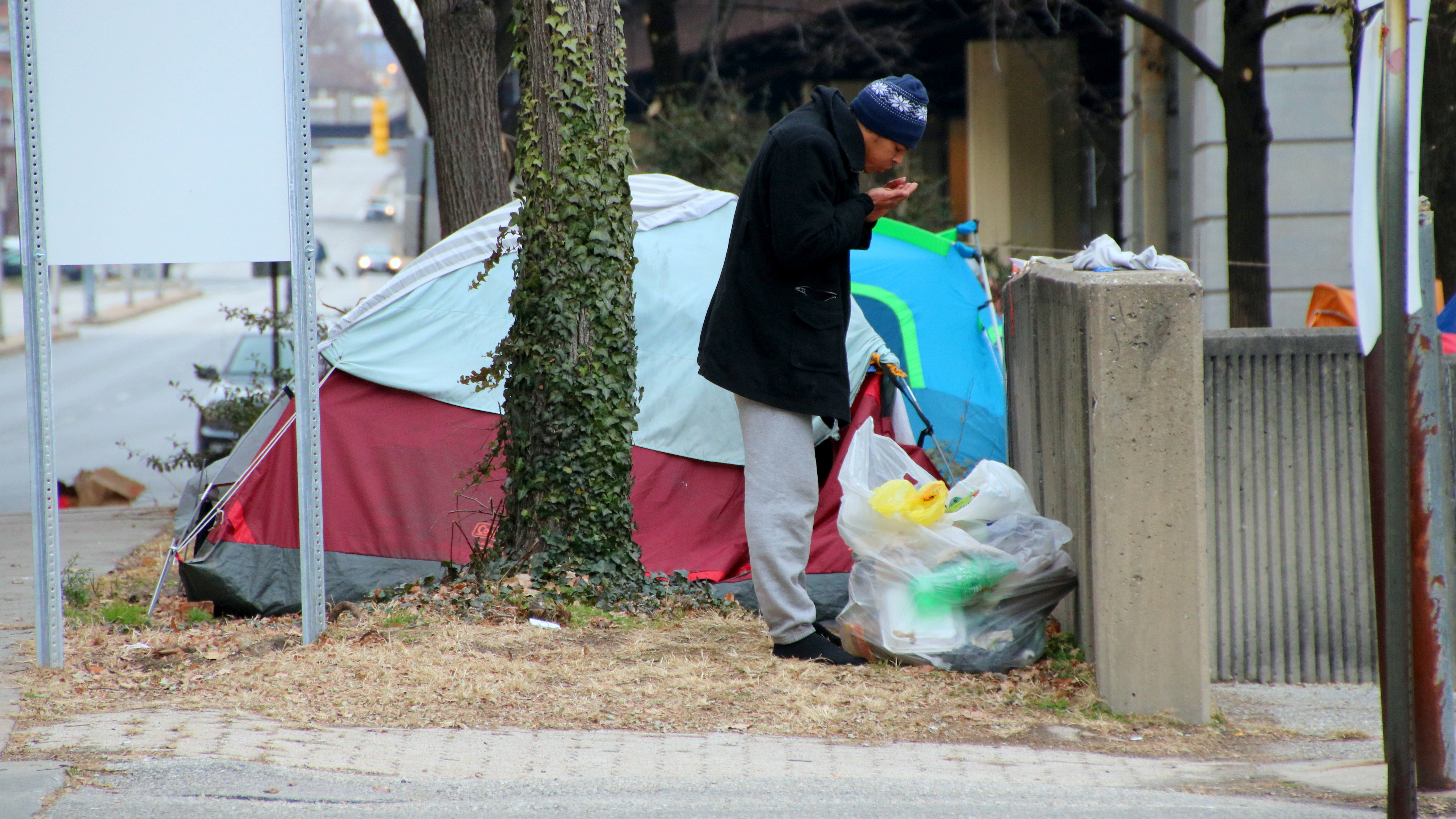 Namid Rawls outside the tent where he has been living for the past month along with about 30 other people, along Guilford Avenue. (Fern Shen)