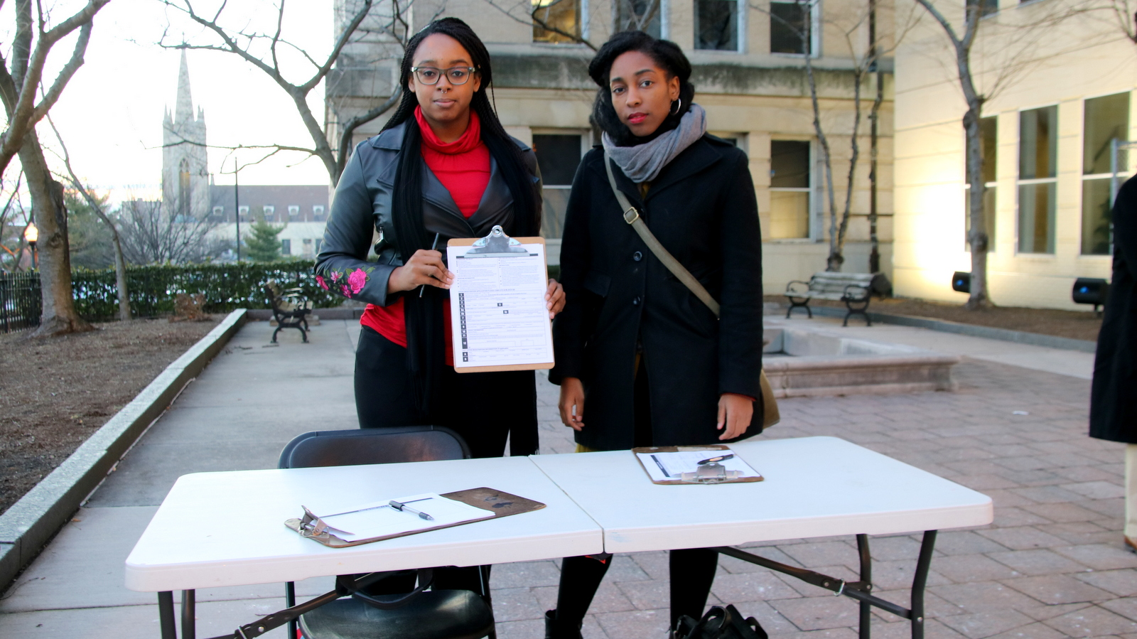 Shamoyia Gardiner and Brittany Oliver, of Not Without Black Women, registered people to vote outside the school board meeting. (Fern Shen)