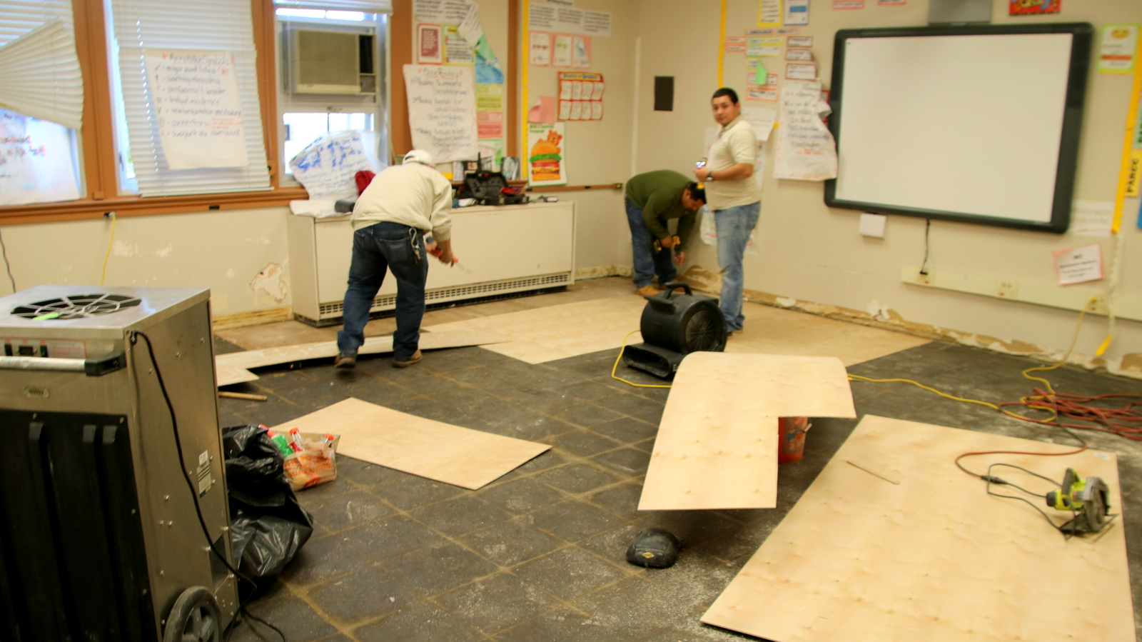 Workers relaying the floor in a flooded classroom at Frederick Douglass High School. (Fern Shen)