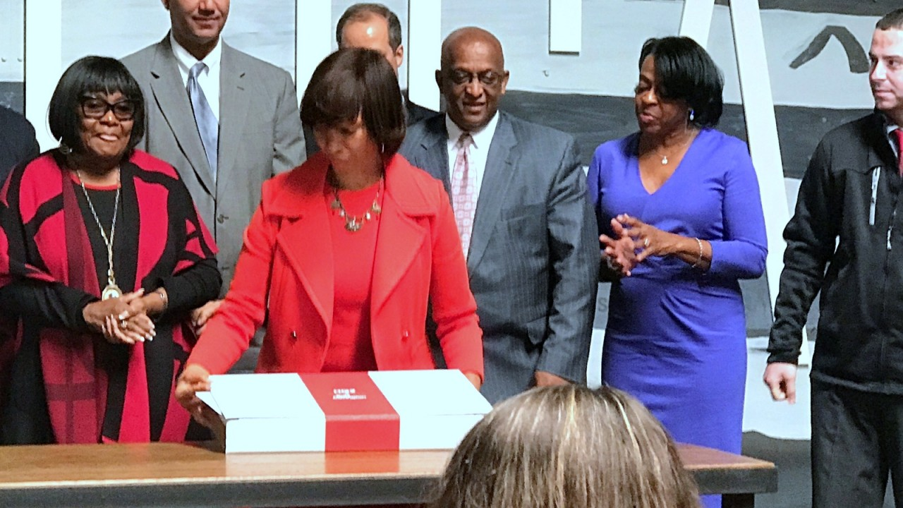 Mayor Catherine Pugh signing Port Covington's Amazon HQ2 proposal surrounded by city and state officials last October. (Mark Reutter)