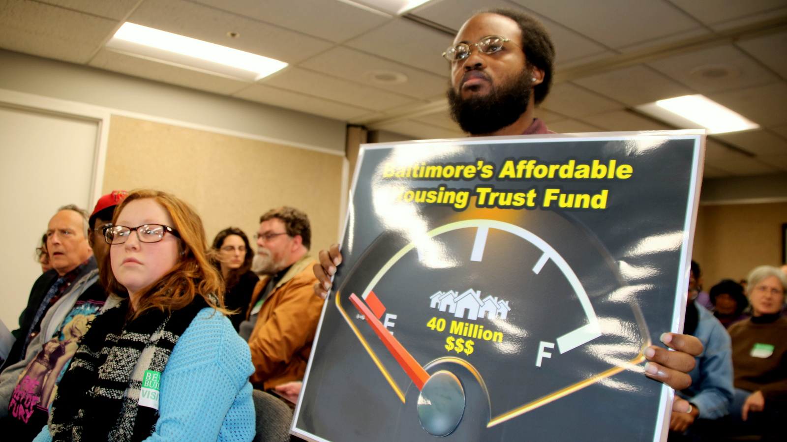 Terrel Askew stands with other members of the Baltimore Housing Roundtable at a capital budget hearing for the Department of Housing. (Fern Shen)