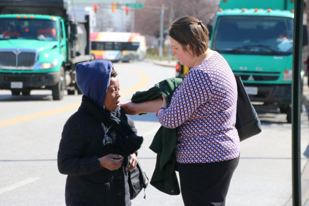 Attorney Karen Wabeke of the Homeless Persons Representation project comforts Donna after helping her move her belongings out of the roadway. (Fern Shen)