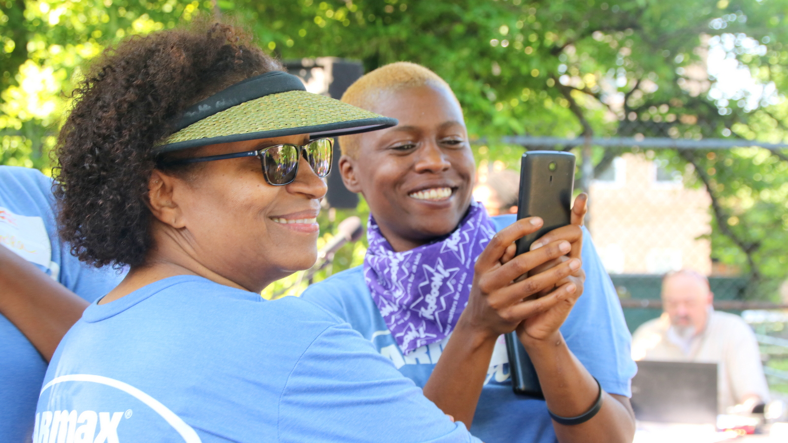 Neighborhood volunteers Charlene Couch and Kisha Scott capture the moment as the playground build begins. (Fern Shen)