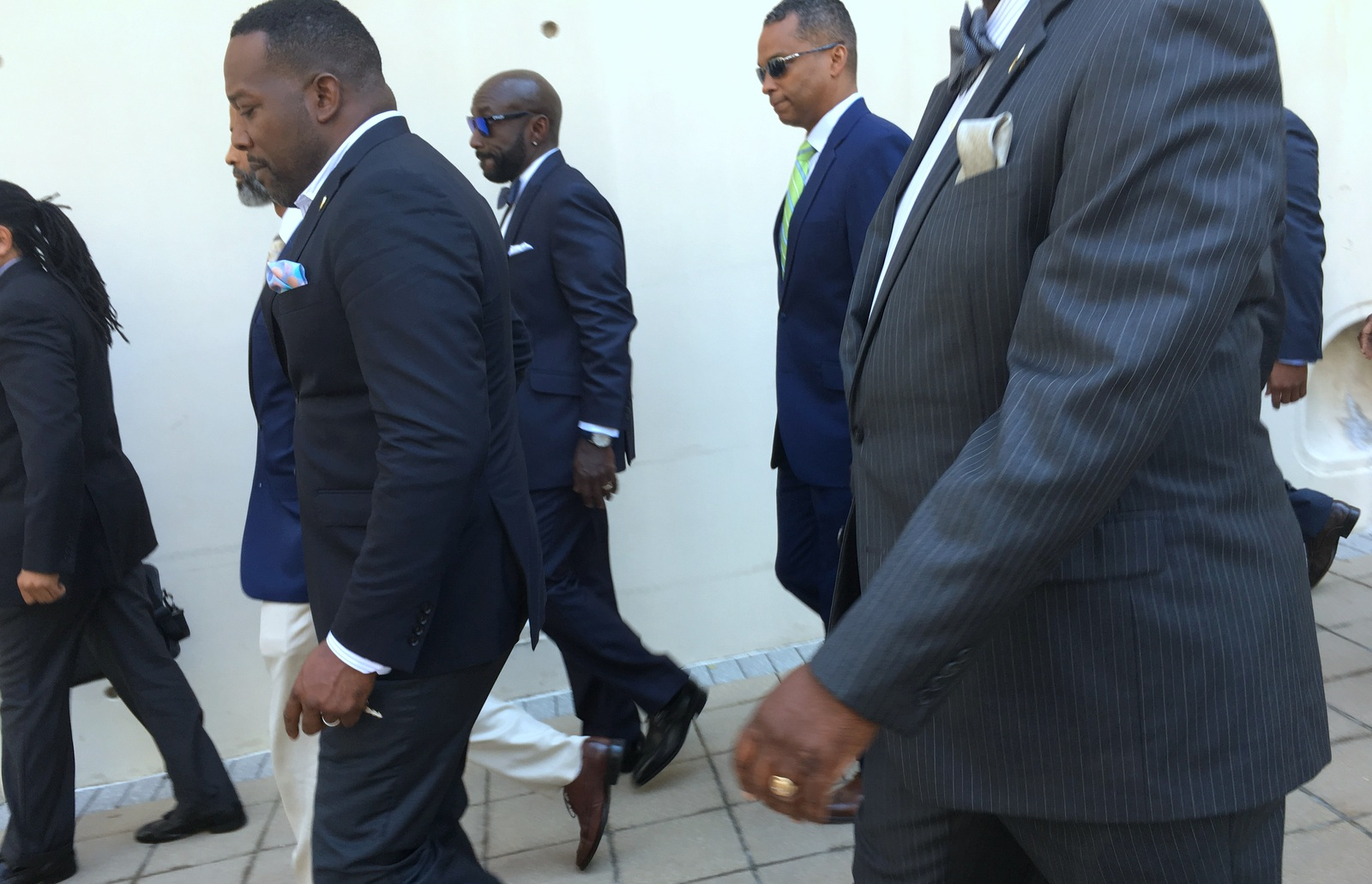 Darryl De Sousa (in green tie) leaves the courthouse this afternoon with his supporters. (Fern Shen)