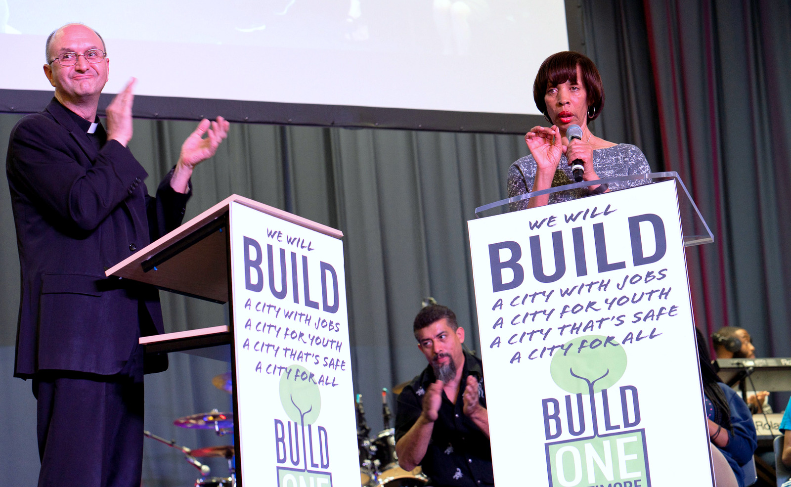 Mayor Pugh wins the applause of Father Bruce Lewandowski of the Sacred Heart of Jesus Church, who brought a large contingent of immigrant parishioners to last night's meeting. (Julia Pearson/BUILD)