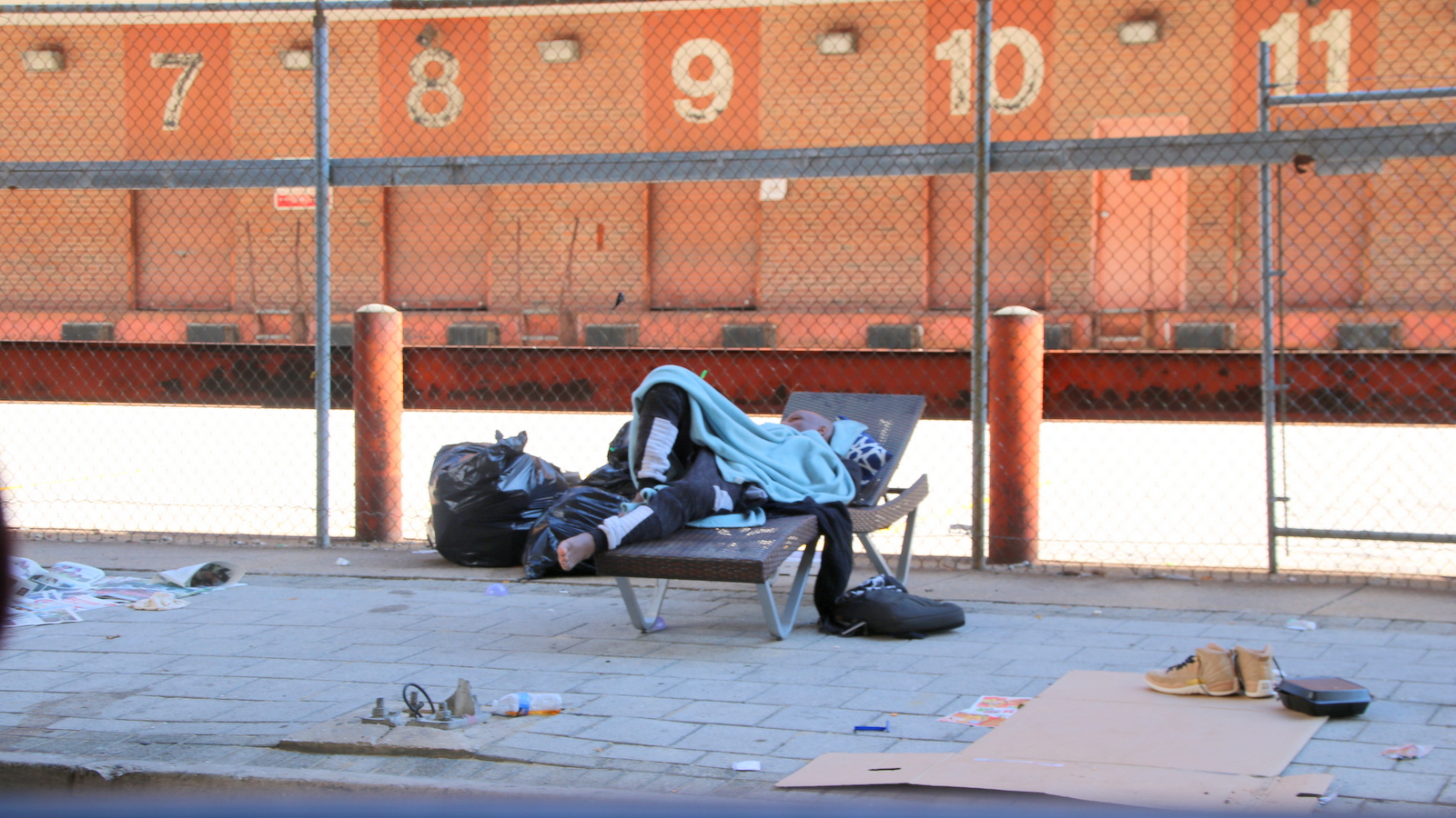 A man sleeps on a cot next to the Baltimore Sun's loading dock on bath Street. (Fern Shen)