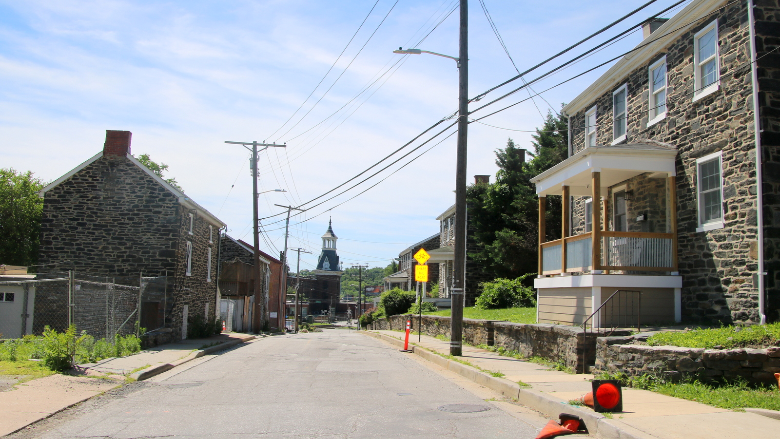 The view today on Clipper rRoad, with the stone houses at left, other stone buildings at right and the mill buildings visible at the bottom of the hill. (Fern Shen)