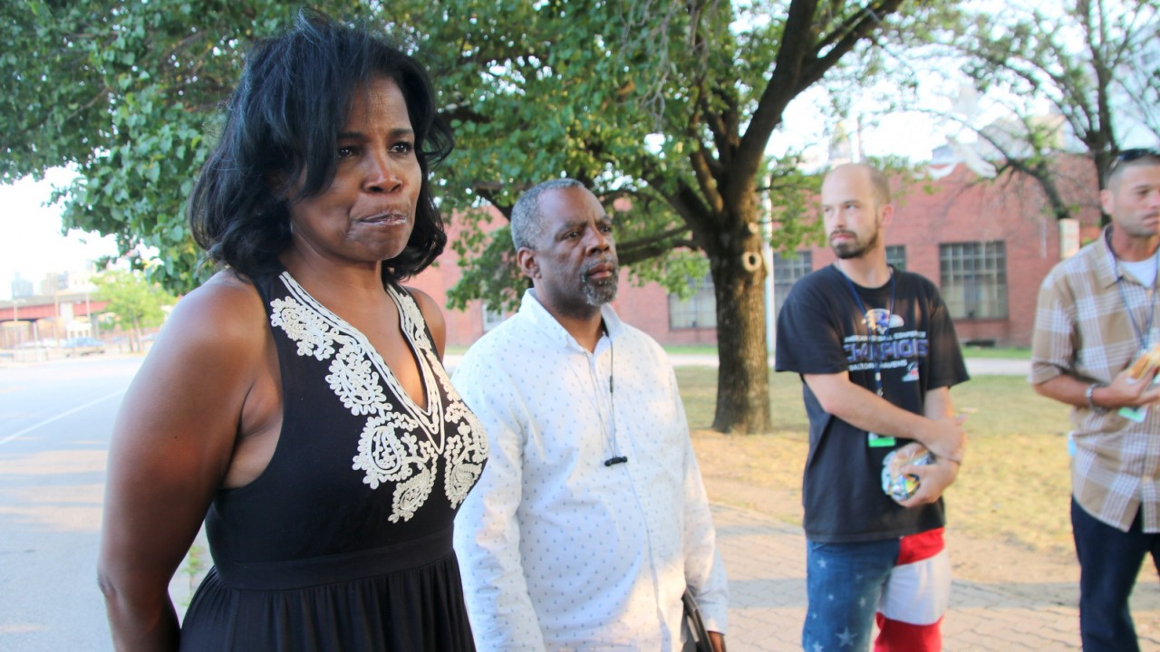 Angel Settle attends a prayer vigil last Friday in the small park on Fallsway and Centre Street where her sister was found dead. (Fern Shen)