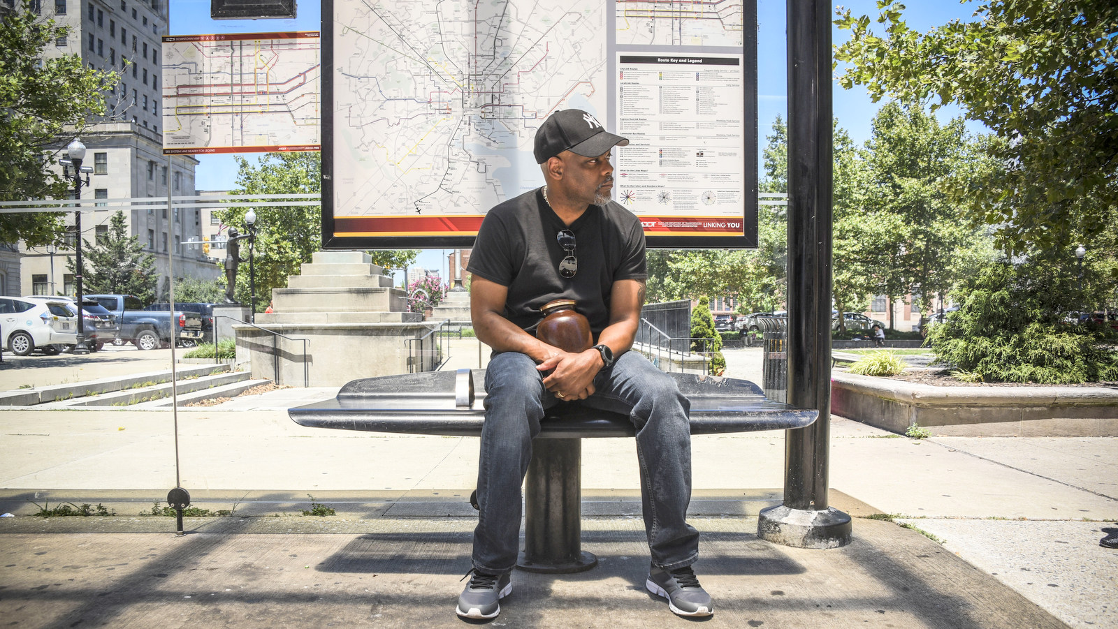 Holding his brother's ashes, Daniel Alexander, sits on the bus bench on East Fayette Street where Lawrence Alexander spent his last night. (Joe Giordano)