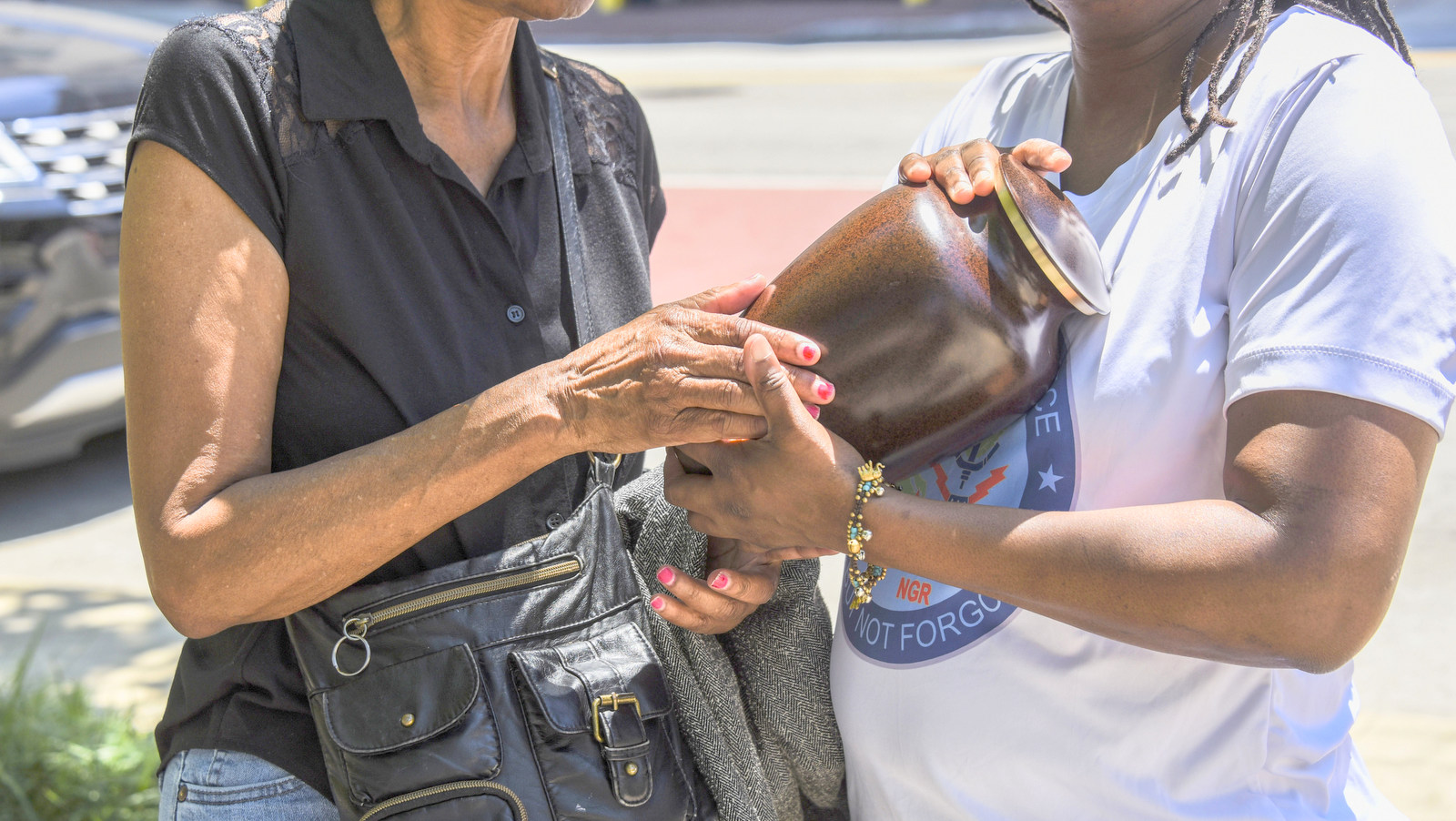 Lawrence Alexander's mother, Teresa Singleton, and sister, Faith Alexander, hold his ashes outside at the place where he was found dead, near a bus bench outside Baltimore City Hall. (J.M. Giordano)