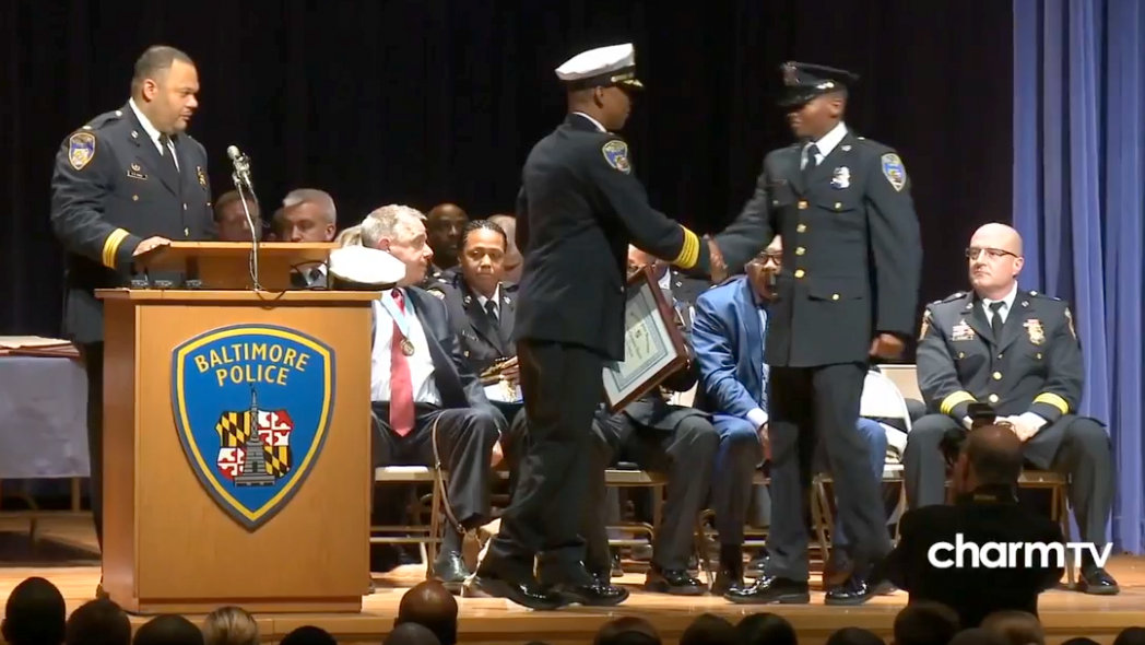 Then-commissioner Darryl De Sousa hands an award to Officer Arthur Williams at a baltimore police academy graduation ceremony in April. (YouTube)