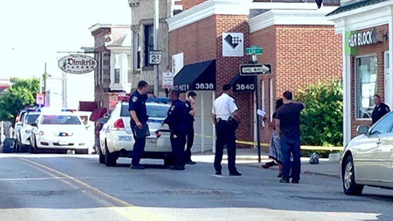 Police examine the corner of Cox Street and Falls Road where the 12-year-old was struck by a police cruiser. (WMAR)