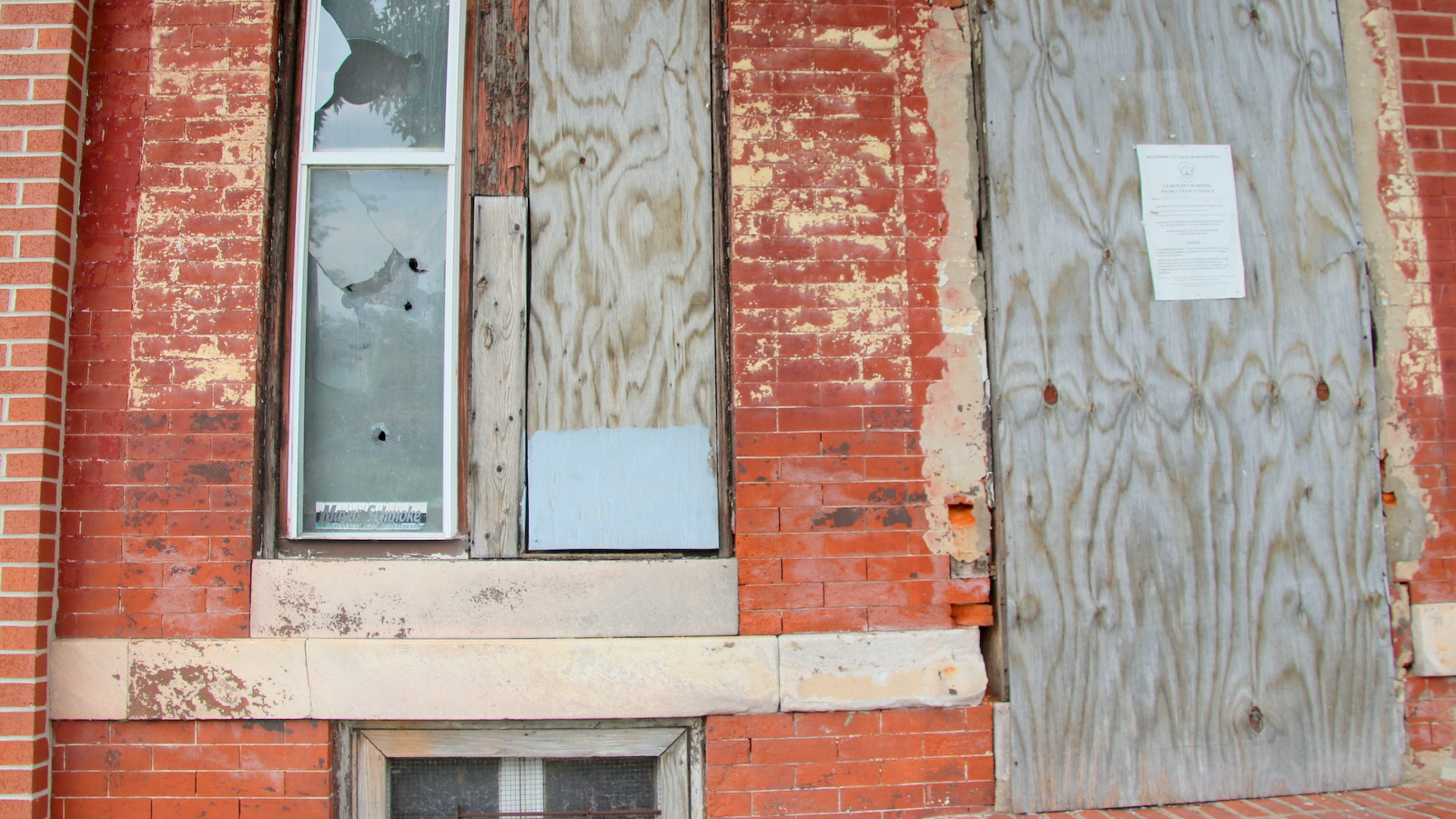 Near where Det. Suiter was shot, some houses are occupied but many more are vacant and boarded-up, like this one on West Franklin Street. (Fern Shen)