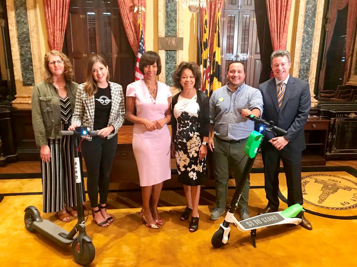 Mayor Catherine Pugh (pink dress) and DOT director Michelle Pourciau (to her left) pose with Bird and Lime scooters. (@MayorPugh50)