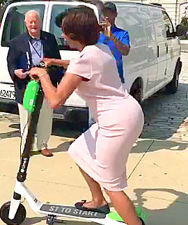 In a rare public appearance, Jim Smith watches the mayor try her hand at scooting in a City Hall photo op last month. (@limebike)