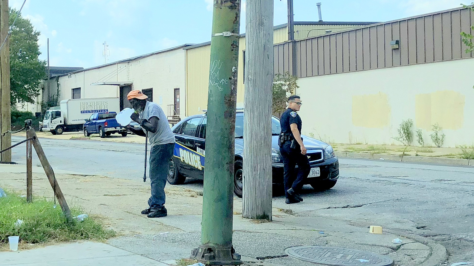 City police officer gives a man water on a hot day in Baltimore last week. (Fern Shen)
