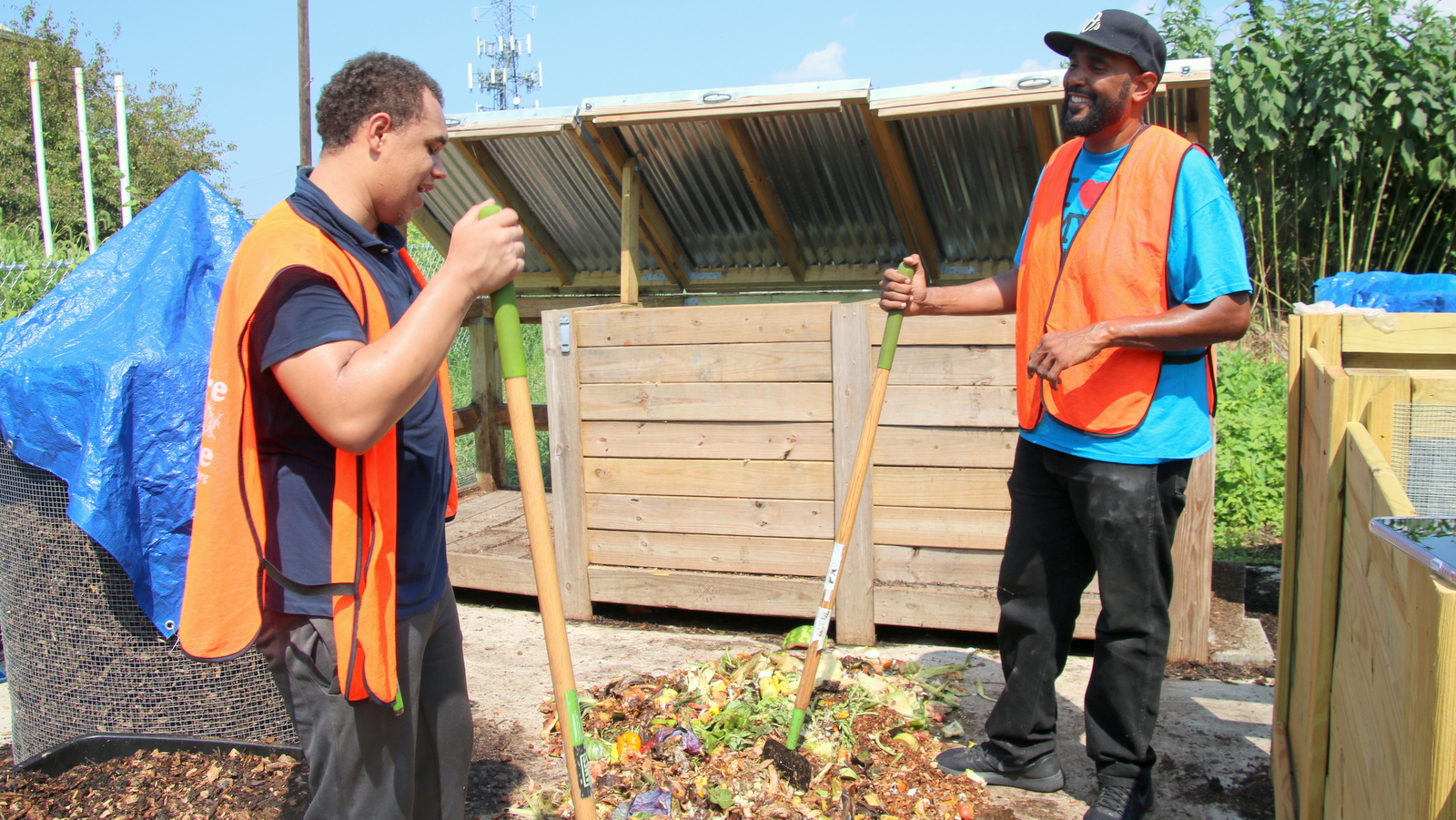 From left, Anthony Walton and Marvin Hayes, of the Baltimore Compost Collective, chop food waste. (Fern Shen)